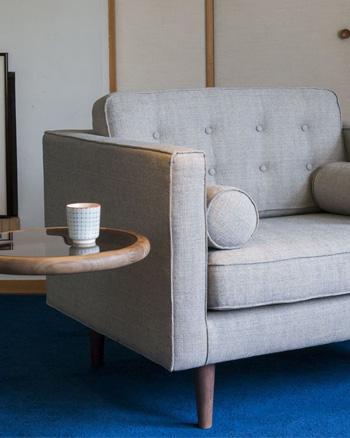 fauteuil gris tissu capitonné