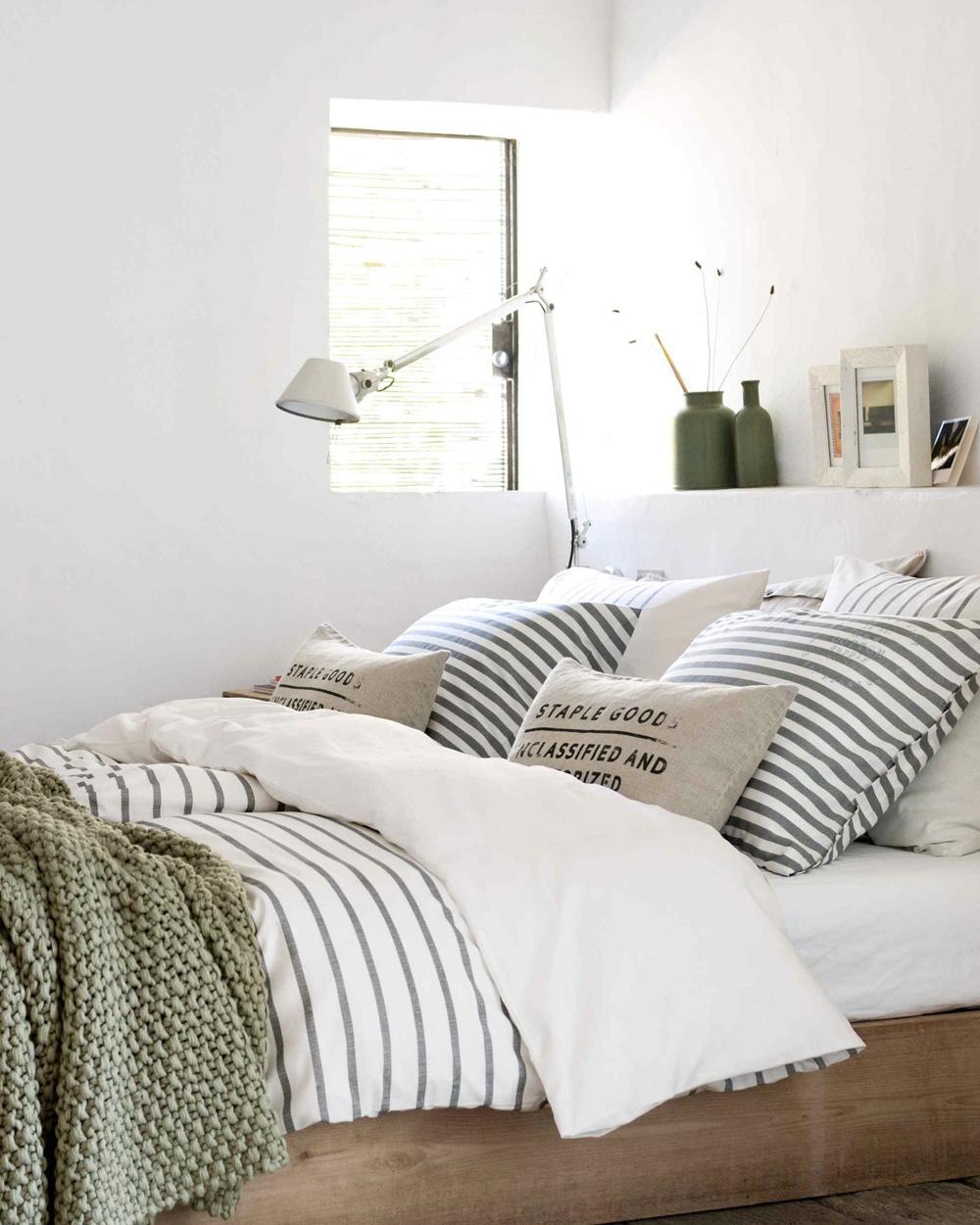 plaid en tricot vert olive dans chambre blanche